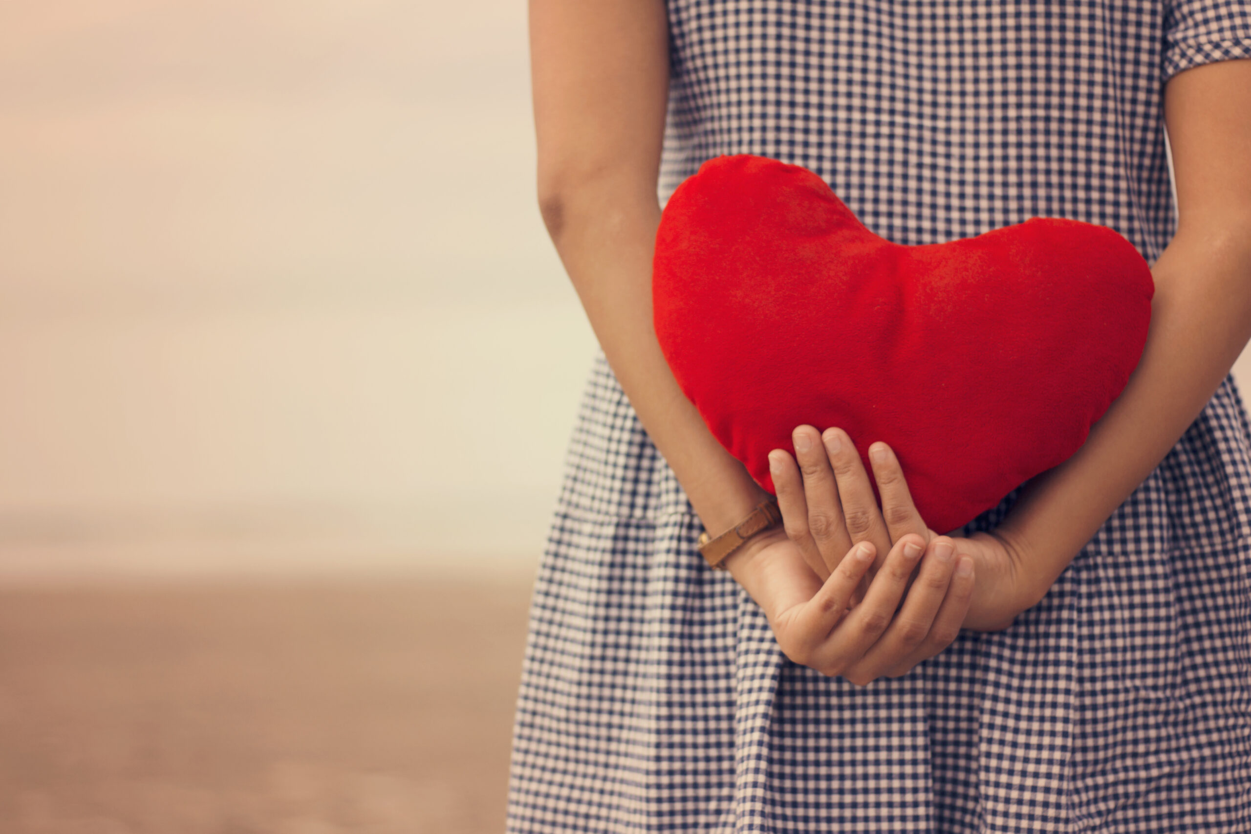 Woman holding a red heart on the beach