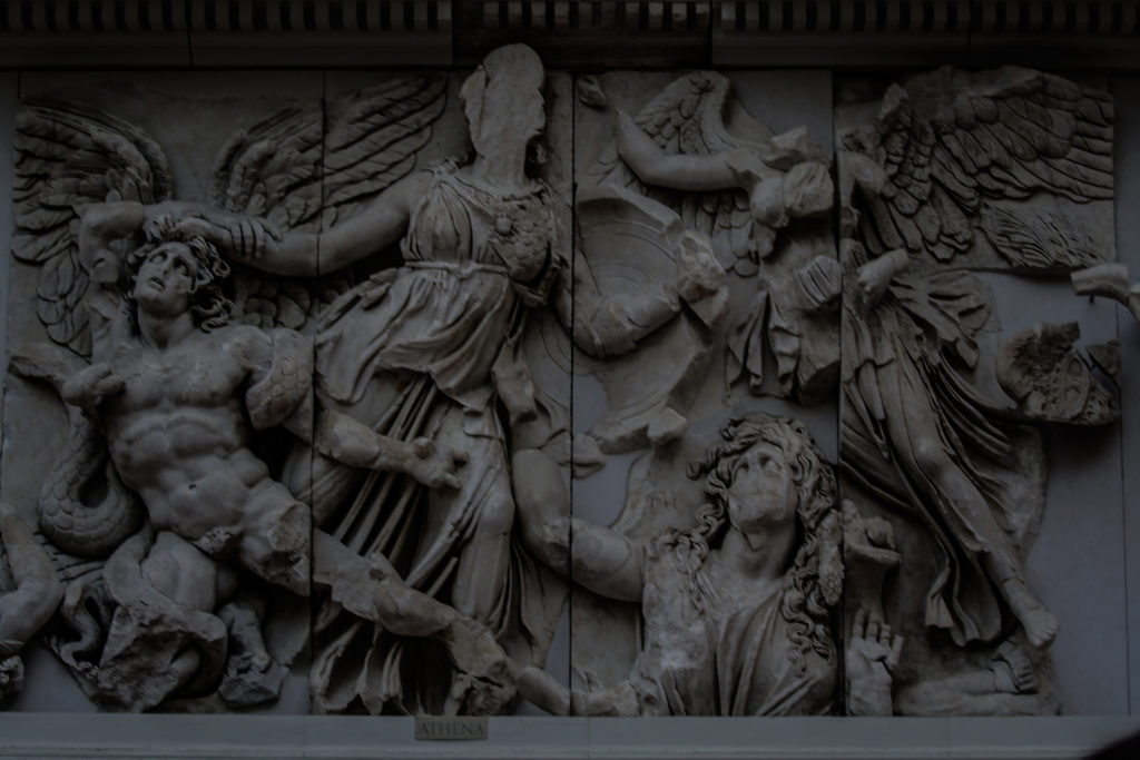 Pergamon Altarpiece. Built by order of Eumenes II Soter. 164-156 B.C. by artists of the school of Pergamon. Marble and Limestone. East frieze. Gigantomachy. Struggle between gods and giants. Athena taking the young Alcyoneus by the hair while his mother, Gaia leaves the ground due to the death of her son. Next, the winged Nike. Pergamon Museum, Berlin, Germany