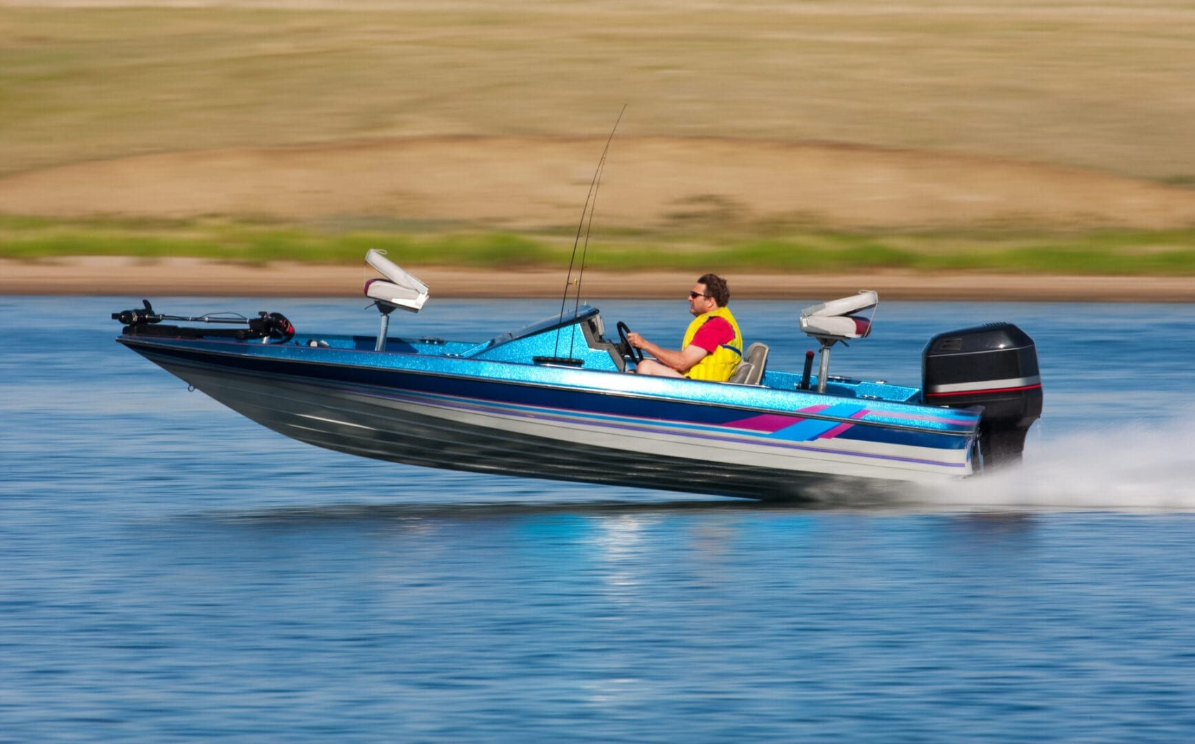 Man driving a fast boat with panned (motion blur) background