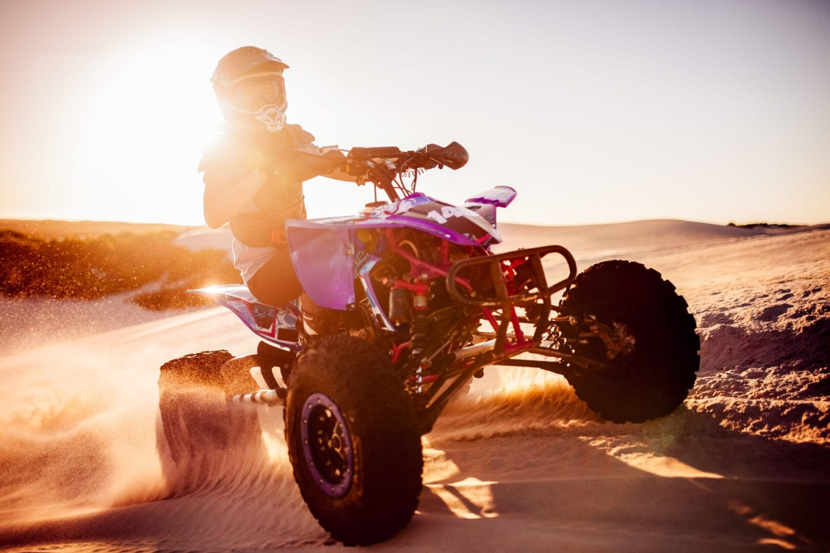 Quad biker in desert race with sun flare