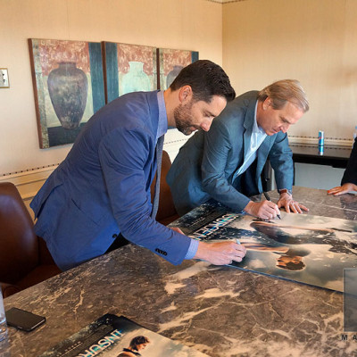 Mandeville Films EP Todd Lieberman signing Insurgent posters with co-producer Douglas Wick.