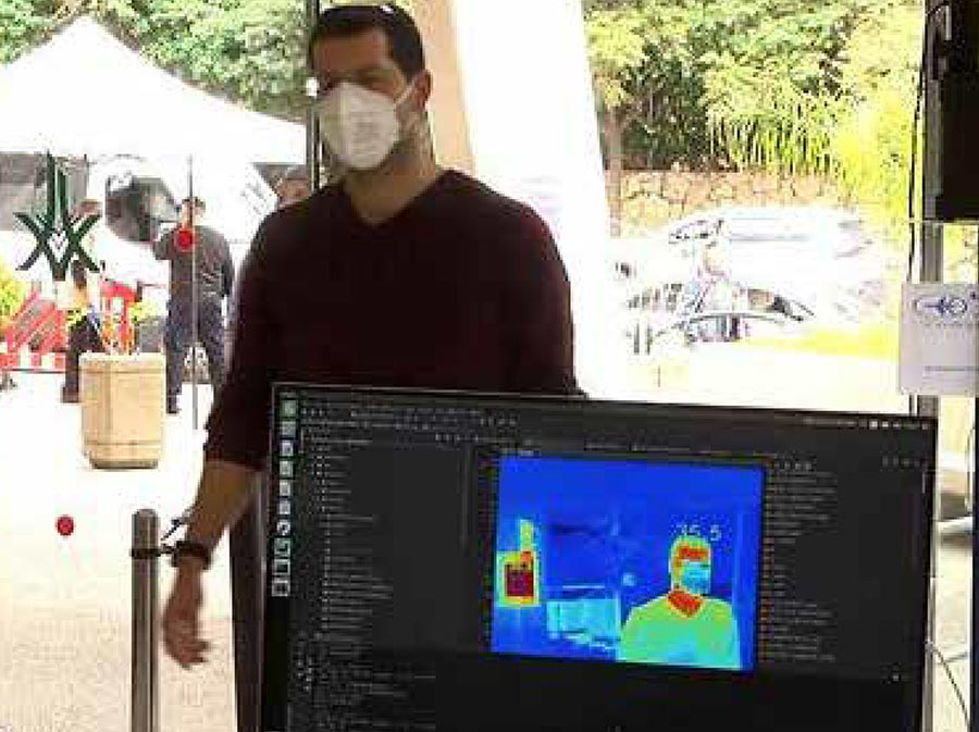 Thermal scanning machine taking a man's temperature as he walks through the entrance