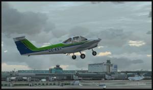 Piper Tomahawk PA-38 au décollage de la piste 28 avec, en arrière-plan, le terminal de l'aéroport international Montréal Pierre-Elliott-Trudeau (FSX)