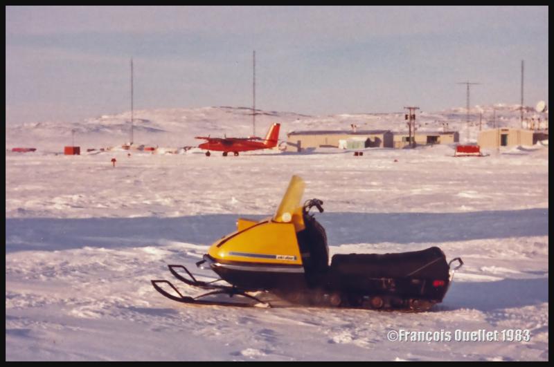 Le Twin Otter de Bell Canada, au second plan, lors d'une belle journée d'hiver à Inukjuak. Au premier plan, un modèle de ski-doo de l'époque.
