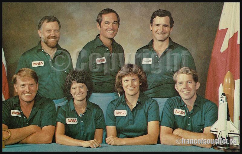 L'astronaute canadien Marc Garneau (rangée du haut, extrême droite) et les astronautes américains choisis par la Nasa pour la mission 41-G avec la navette spatiale Challenger (de gauche à droite et de bas en haut: Jon A.McBride, Sally K. Ride, Kathryn D. Sullivan, David C. Leestma, Paul D.Scully-Power, Robert L. Crippen, Marc Garneau) sur carte postale aviation.