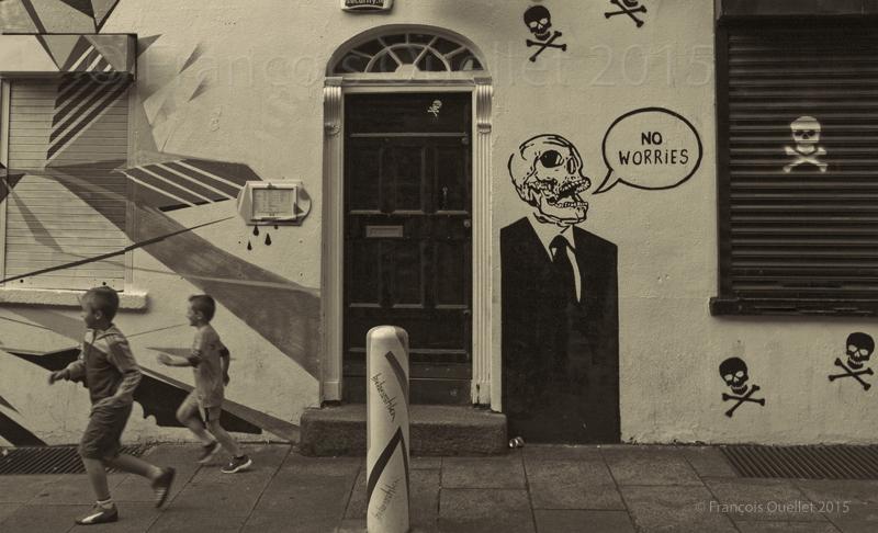 Des enfants jouent dans un quartier de Dublin où des squelettes décorent les murs des bâtiments.