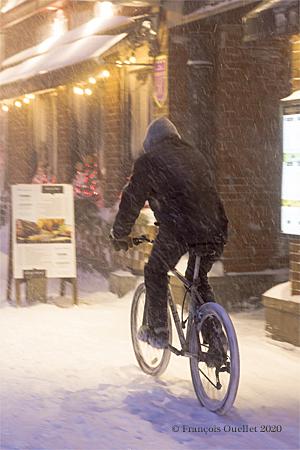 Un cycliste circule sur un trottoir du Vieux-Québec durant la tempête de neige du 7 février 2020.