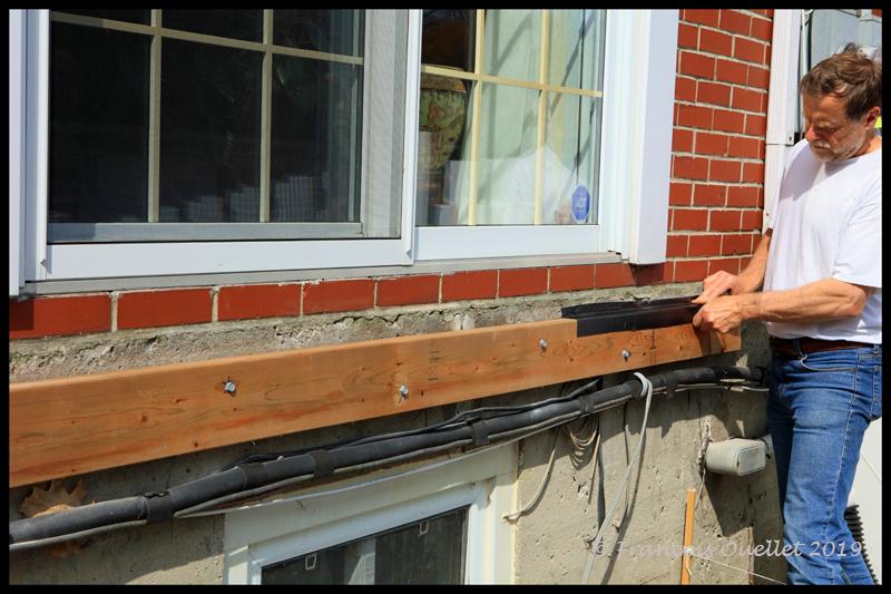 Pose de la première pièce de bois qui recevra la terrasse.