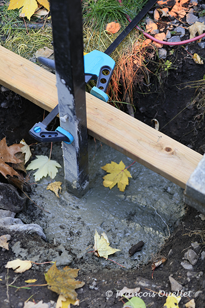 Le ciment est coulé pour fixer le poteau de clôture.