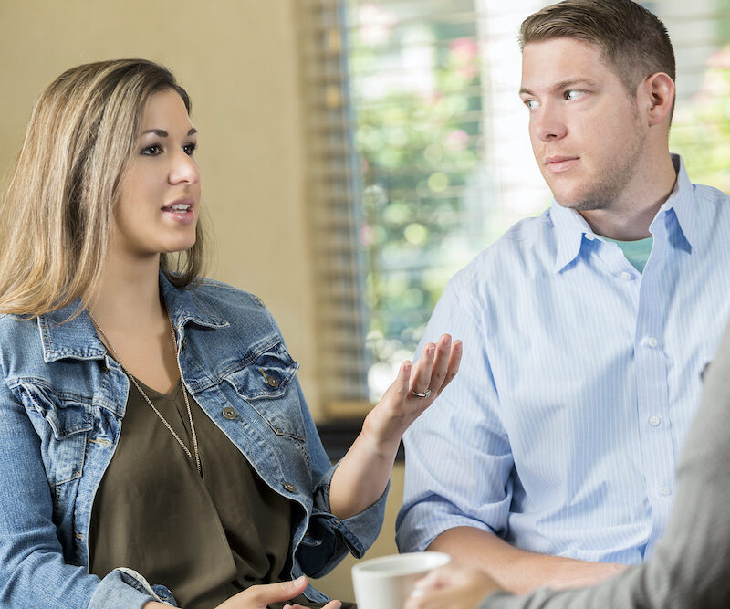 Pretty mid adult Hispanic woman gestures while talking to a marriage counselor. She has a concerned expression on her face while she speaks. Her husband is looking at her. Only the counselor's arm is seen in the photo.
