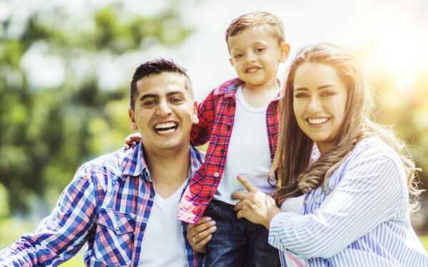 Happy young family looking at camera