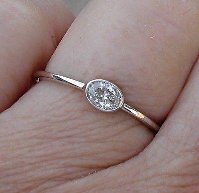 oval bezel east-west engagement ring