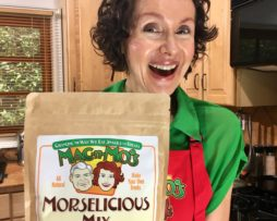 Health coach, Mo The Morselist, is in a green top and red apron. She's smiling while holding a bag of her Mac-n-Mo's Morselicious baking and cooking mix while standing in a kitchen.