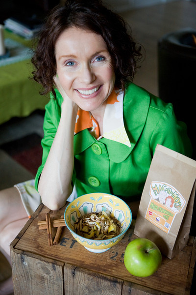 Certified Health Coach and professional recipe developer, Mo The Morselist poses in a bright green jacket at a table. On the table is a bowl, a green apple, cinnamon sticks, and a bag of her Morselicious cooking and baking mix.