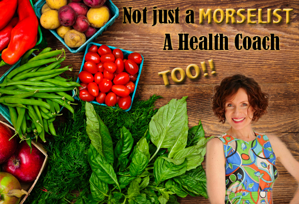 Health coach, Mo The Morselist, stands next to an arrangement of rainbow vegetables.