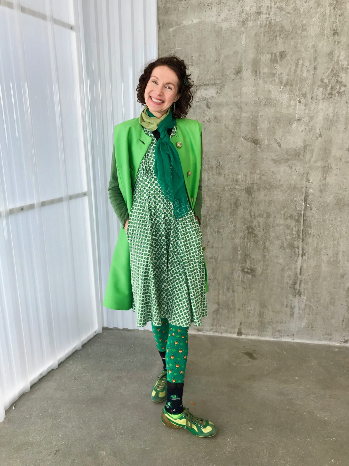 Health coach, Mo The Morselist, smiling and posing in a green dress with a green scarf, green leprechaun leggings and socks, and green shoes.