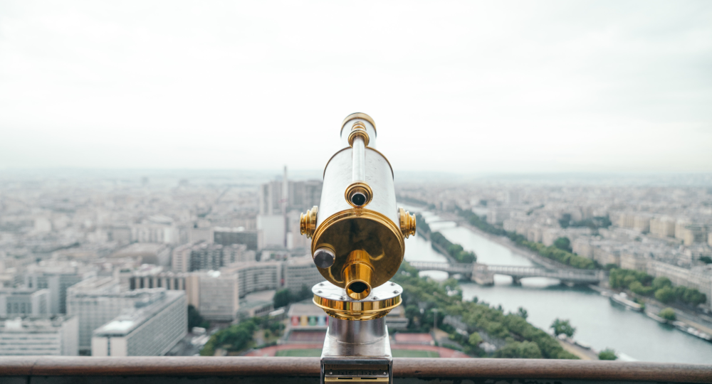 Image of an old-timey telescope overlooking a city scape