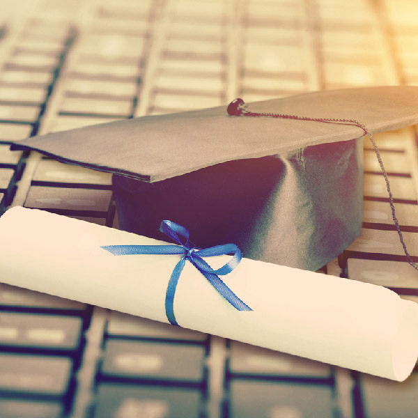 Image of a diploma and hat resting on a keyboard