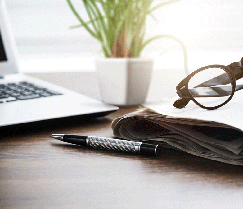 a desk with pot plant, reading glasses, a pen and a newspaper placed upon it