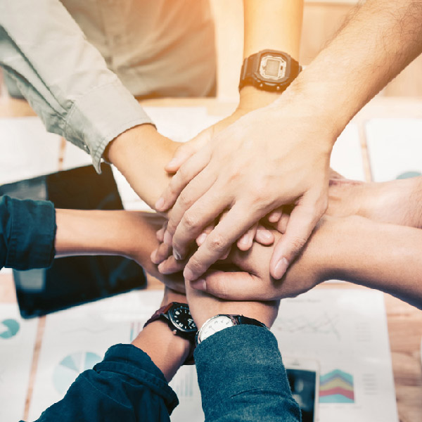 An image of people stacking their hands as part of a team building exercise