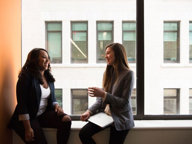 Two women wearing blazers sit on a window sill, smiling and talking.