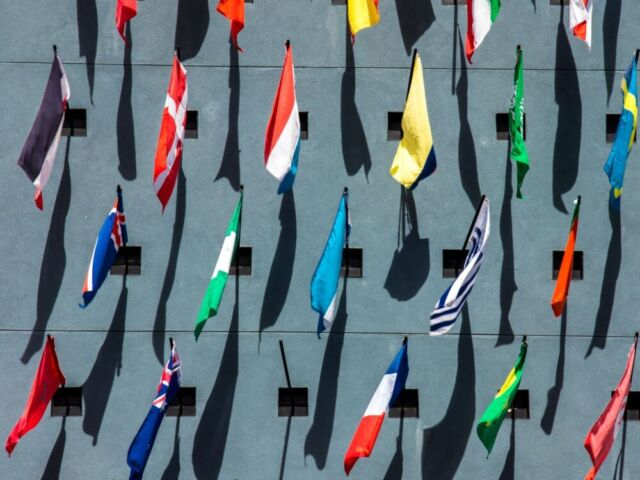 Many national flags on poles as viewed from above