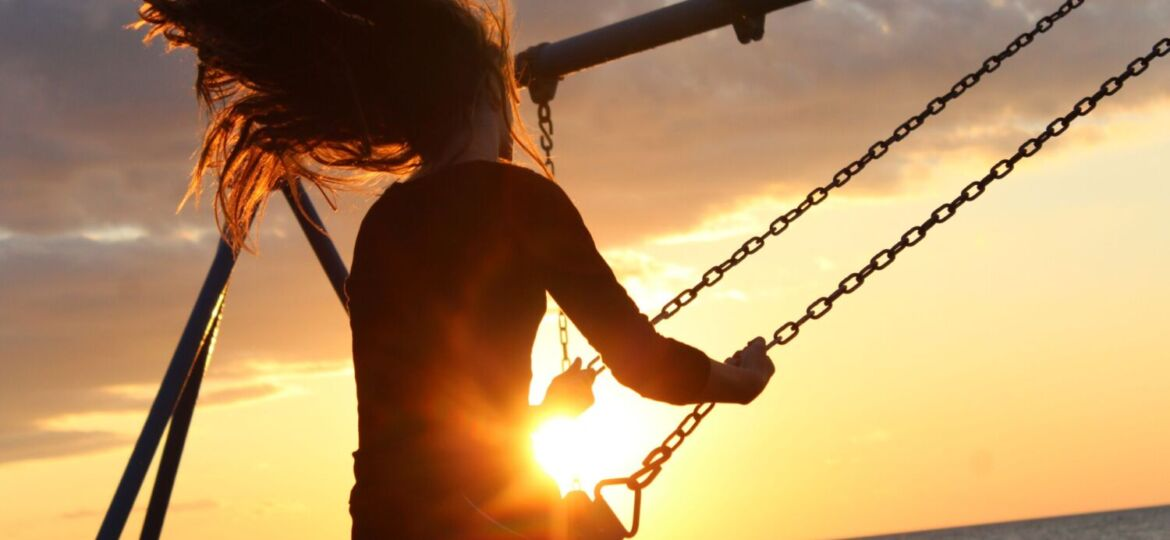 A person viewed from the back swings on a swingset facing the ocean and sunset