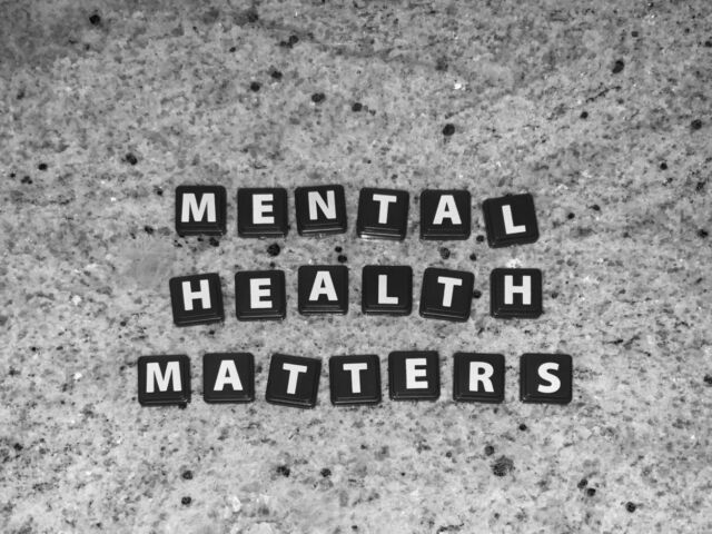 """Letter tiles spell out """"mental health matters"""" on a speckled background."""