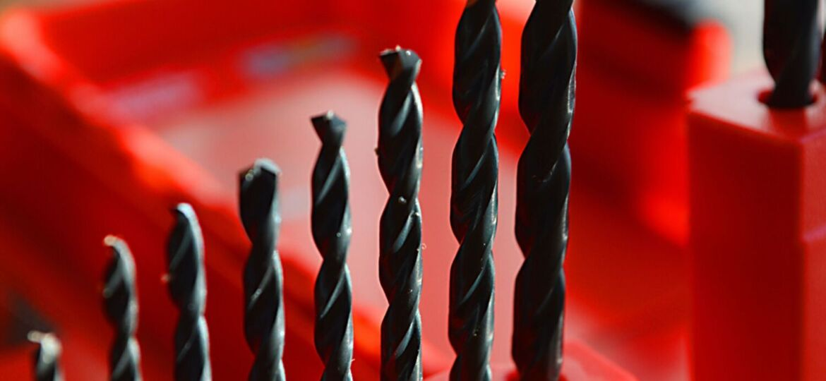 Drill bits rise in a row from small to large, set in a red container.