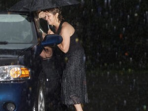 woman locked out of her car at night in the rain waiting for a locksmith