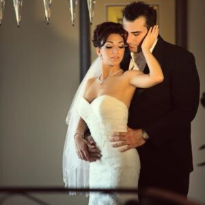 Photo of woman in wedding dress being held from the back by her husband in a black suit
