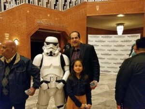 Man standing with a storm trooper and a young elementary school-aged girl at an event