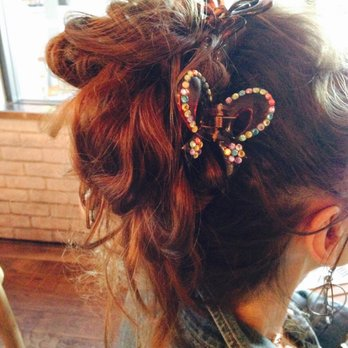 Photo of a womens hair up with a butterfly clip