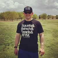 Photo od a man standing in a field with a black hat and black shirt that says squats, bench and deadlifts