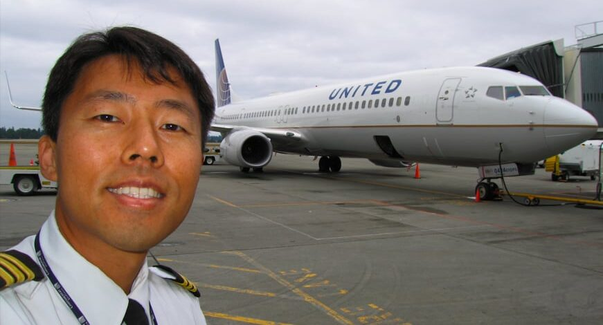 Man with pilot outfit on standing outside in front of an airplane