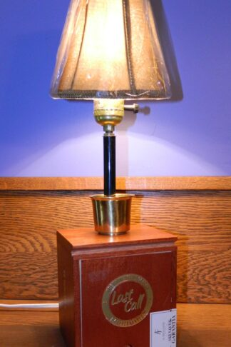 "This lamp is an upright vertical piece created from a wooden Last Call cigar Box. It has a metal ""shot glass"" at the base of the stem and sports a small tan cloth shade on top."