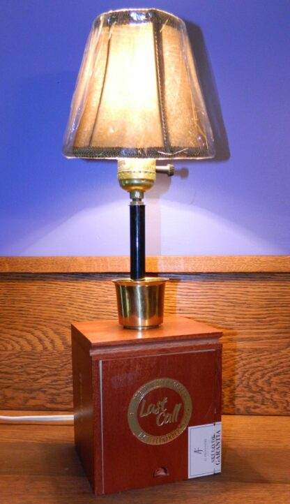 """This lamp is an upright vertical piece created from a wooden Last Call cigar Box. It has a metal """"shot glass"""" at the base of the stem and sports a small tan cloth shade on top."""