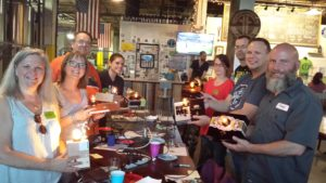 Eight people are are proudly displaying their cigar box lamps. The lamps are lit and everyone is smiling.