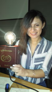 A woman holds her cigar box lamp and smiles in satififaction.