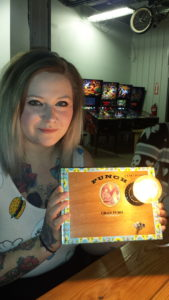 A participant holds up her cigar box lamp creation.