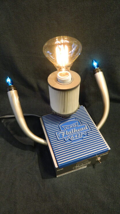 The Flathead 642 Lamp is a blue and silver Lamp built from a CAO Flathead box with automobile details such as pipes and a filter. - For the Car Enthusiast
