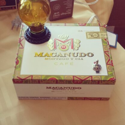 This Macanudo Ciagr Box Lamp is white with green, yellow, and red accents. It's a unique gift for her.