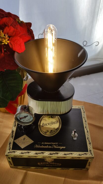 The Future is Now Lamp is Crafted from a Black & Gold Brick House Cigar Box, it shows it's steampunk tenancies with a gauge, an uplight shade and an Edison style bulb.