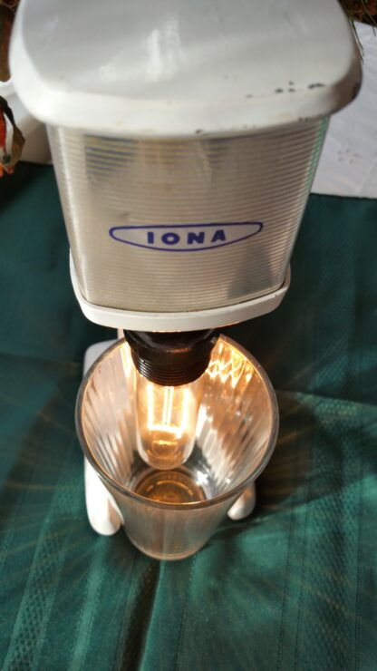 """This lamp is aptly called """"Shake 'Em Up"""" and features a vintage shake maker with cream finish and metallic accents. But where she really shines (pun alert) is when her accompanying pint glass diffuses the light in a hundred different directions."""