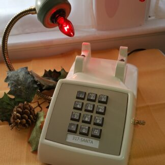 Santa's Hotline is a vintage cream touchstone phone with an avocado green handle. Red Lights glow from the receiver and Santa's Number on the phone. A red and white striped cord adds elegance.