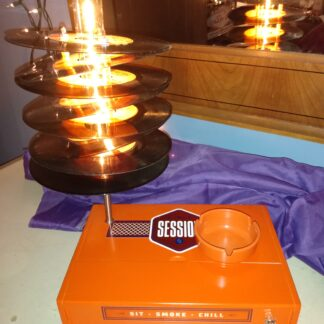 """A bright Orange Session Cigar Box provides the base of this lamp which is topped by a lamp shade made from eight 45 records (with orange and yellow lables) the top 45 reads, """"I still Feel the Same About you."""" Includes handy orange ash tray for candies or other uses."""