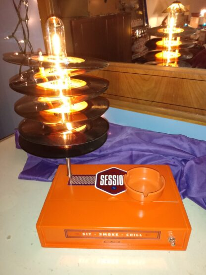 "A bright Orange Session Cigar Box provides the base of this lamp which is topped by a lamp shade made from eight 45 records (with orange and yellow lables) the top 45 reads, ""I still Feel the Same About you."" Includes handy orange ash tray for candies or other uses."