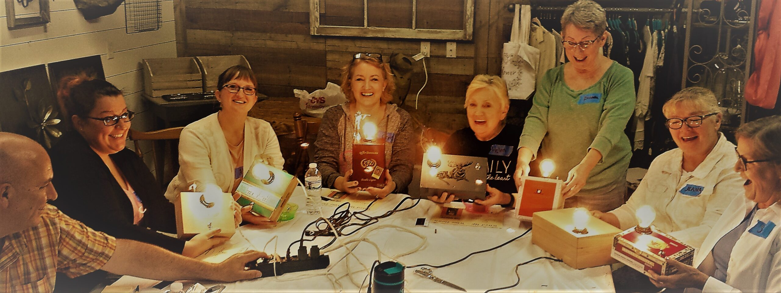 A group of 6 women respond with joy when the switch is flipped and their cigar box lamps light up.