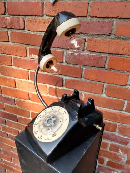 A two-woned cream and black vintage telephone that has two light bulbs coming out of the reciever handle. It's the perfect Wedding Gift!