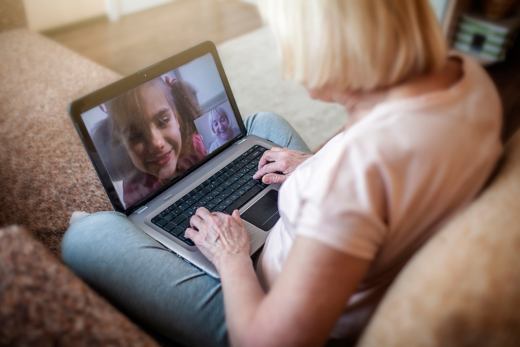 A woman video chats on a laptop with a young girl